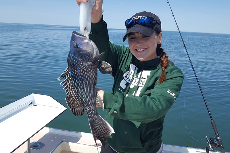 Fishing Charters Young Woman Holding a Sea Bass She Caught on the Flying Connie